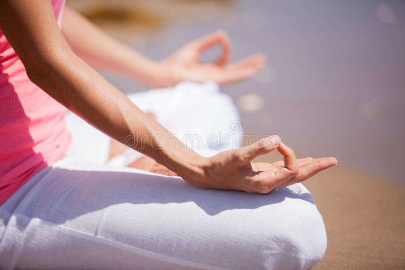 Closeup of a woman meditating. Close look of a woman's body and hands meditating and doing yoga at the beach royalty free stock photo
