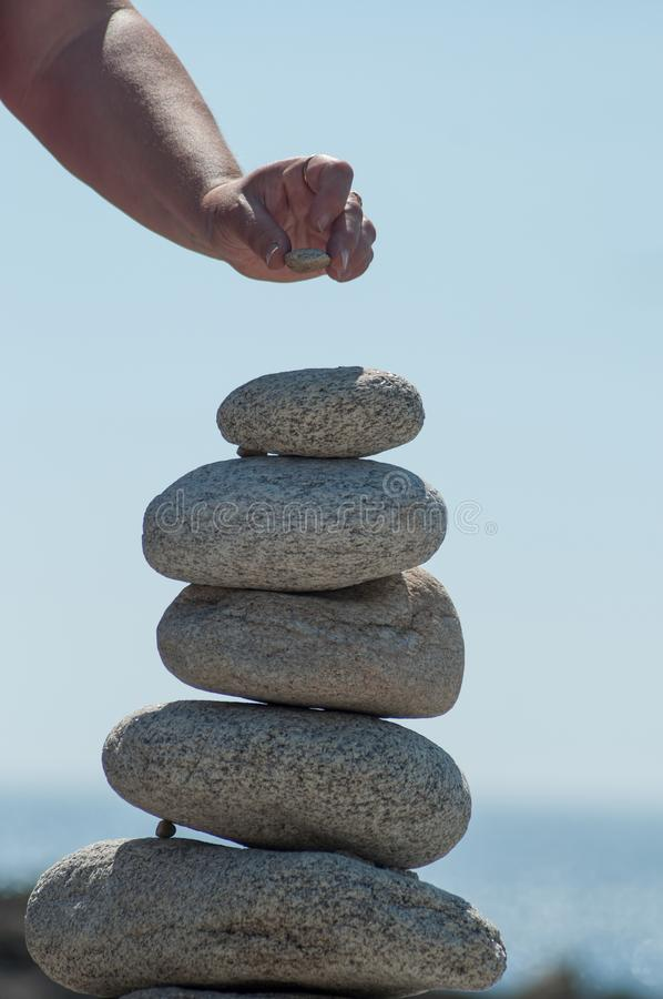 woman putting pebble on stone balance  in border ocean royalty free stock photo