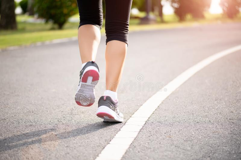 Closeup woman running towards on the road side. Step, run and outdoor exercise activities concept.  royalty free stock photography