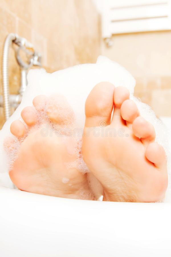 Closeup of woman`s feet covered with foam bubble bath stock images