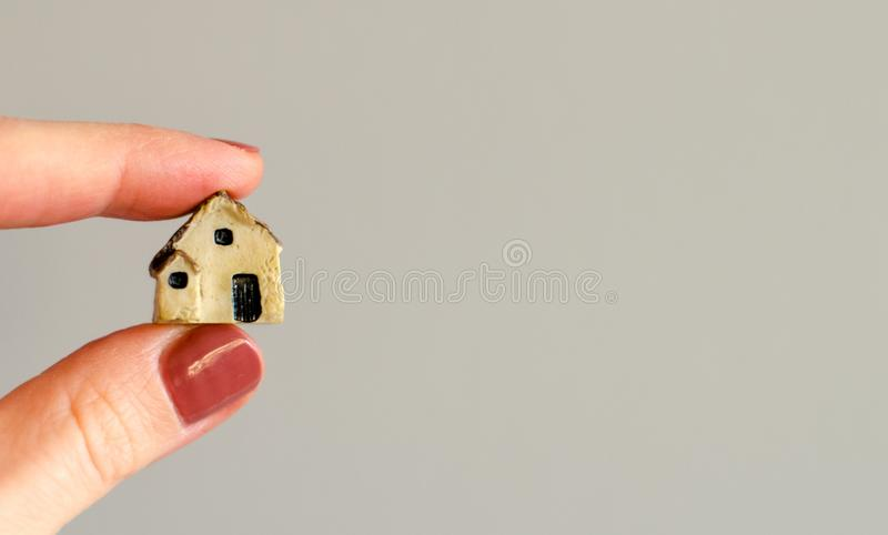 Closeup of woman`s fingers holding tiny plastic house. On blurred grey wall background stock photo
