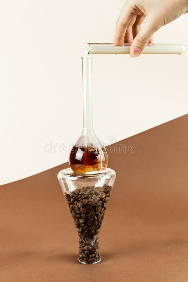 Closeup of woman`s hand holding test tube with oat milk pouring it into flask with coffee on conical glassware stock image