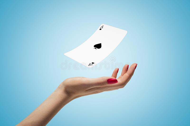 Closeup of woman`s hand levitating ace of spades on light blue background. royalty free stock image