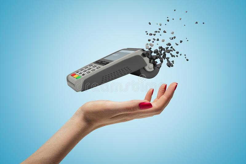 Closeup of woman`s hand levitating point-of-sale terminal which has started to break into small pieces on light blue. Background. Graphic design. Retail royalty free stock images