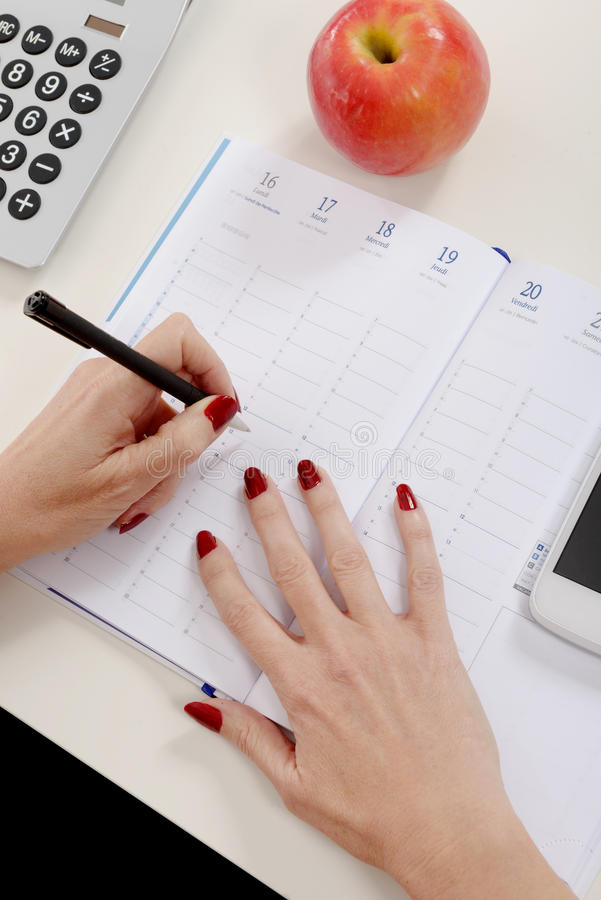 Closeup of woman's hand writing on organizer. A closeup of woman's hand writing on organizer stock photography
