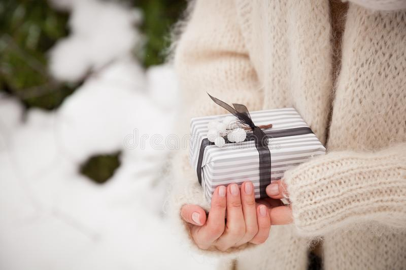 Closeup of woman`s hands holding a nice Christmas present. Outdoors. Celebration. Holidays, gifts and winter concept.  royalty free stock images