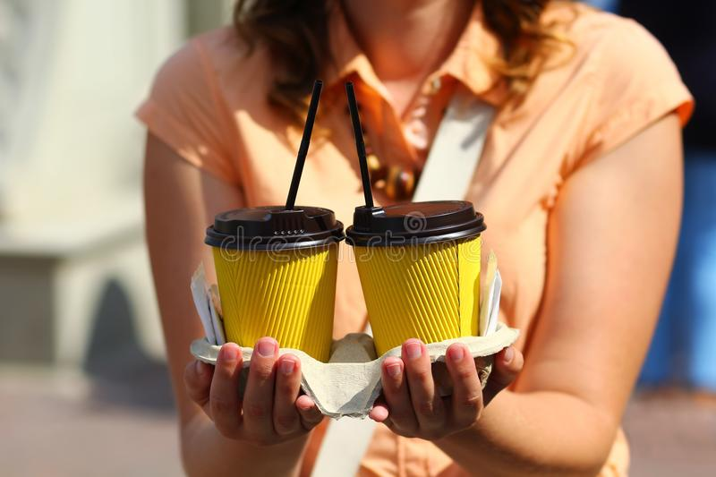 Closeup of woman`s hands holding two corrugated yellow plastic coffee cups. mockup, royalty free stock photo