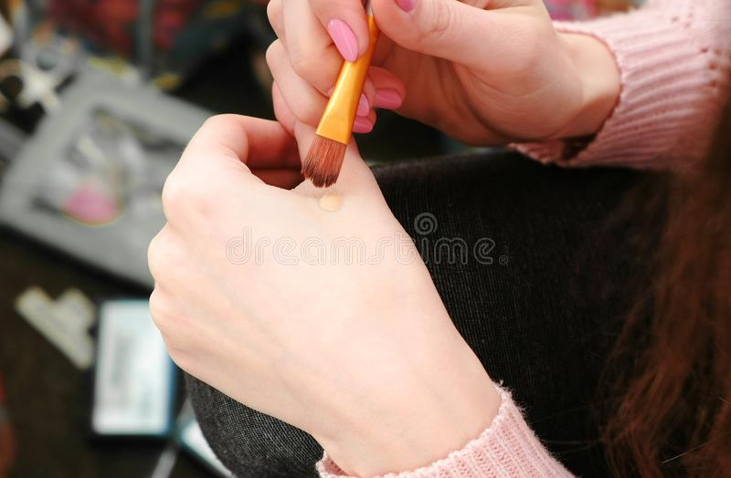 Closeup woman`s hands put the tonal cream on the face with brush to do a makeup before the mirror. stock photography