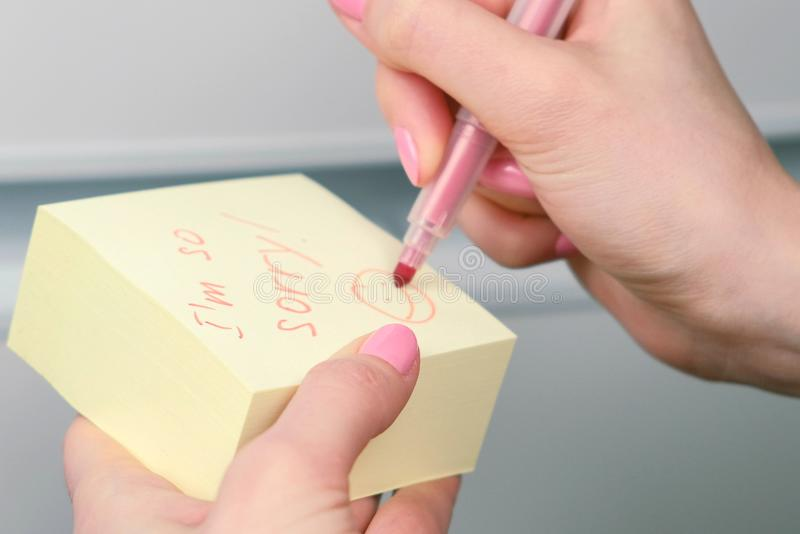 Closeup woman`s hands write on yellow sticker paper sheets words i`m so sorry and laugthing emoticon. royalty free stock photo