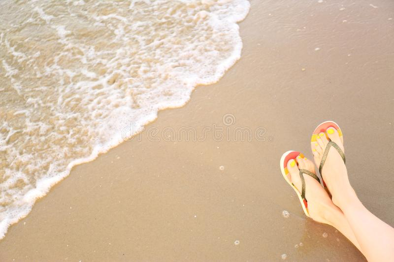 Closeup of woman with stylish flip  on sand near sea, space for text. Beach accessories. Closeup of woman with stylish flip flops on sand near sea, space for royalty free stock image