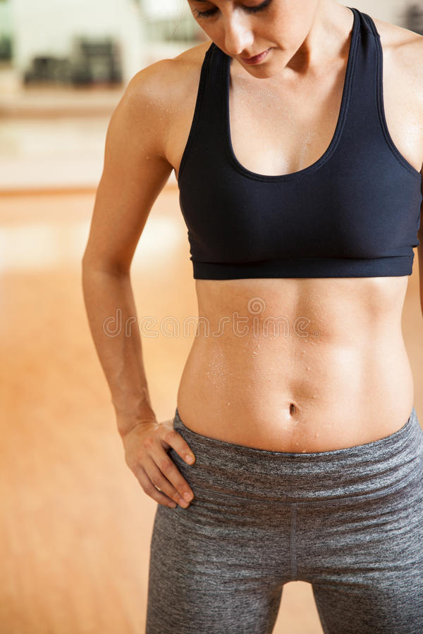 Closeup of a woman with sweaty abs royalty free stock images