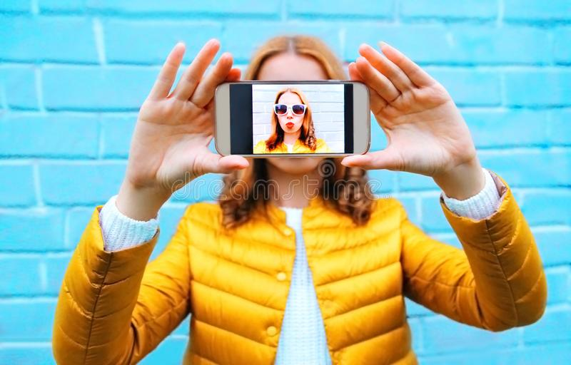 Closeup woman takes picture self portrait on smartphone on blue royalty free stock photography
