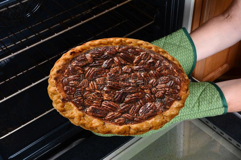 Closeup of a woman taking a fresh baked Pecan Pie from the oven. Horizontal showing the womans hands in oven mitts only stock image