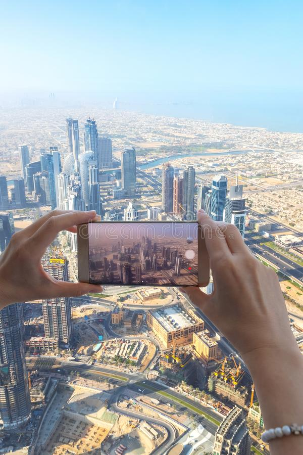 Closeup of woman tourist hand taking photo of Dubai city with smartphone camera from Burj Khalifa tower. stock photo