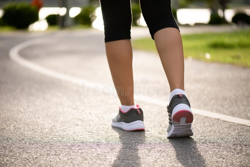 Closeup woman walking towards on the road side. Step, walk and outdoor exercise activities concept.  stock photo