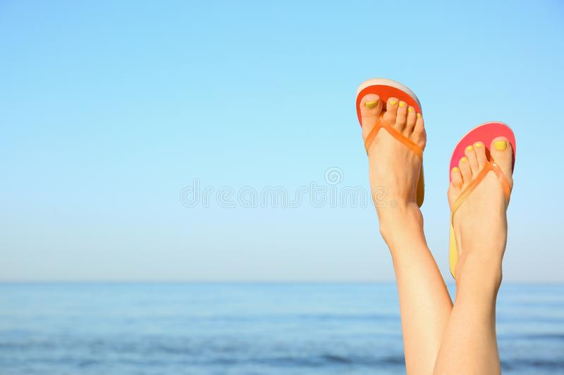 Closeup of  wearing flip flops near sea, space for text. Beach accessories. Closeup of woman wearing flip flops near sea, space for text. Beach accessories stock photo