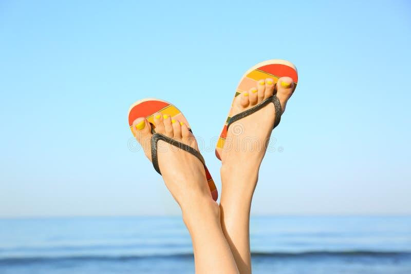 Closeup of woman wearing flip flops near sea. Beach accessories. Closeup of woman wearing flip flops near sea, space for text. Beach accessories royalty free stock photo