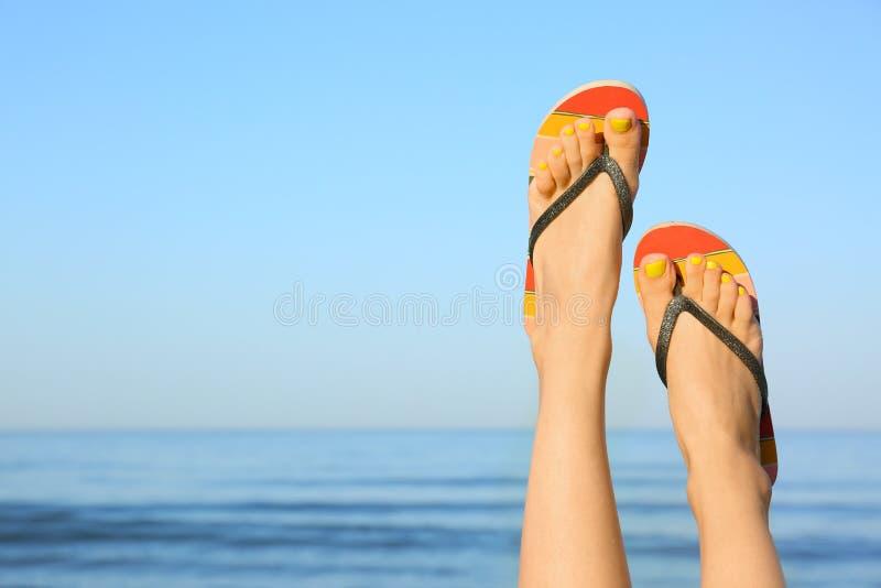 Closeup of woman wearing flip flops near sea. Beach accessories. Closeup of woman wearing flip flops near sea, space for text. Beach accessories royalty free stock photos