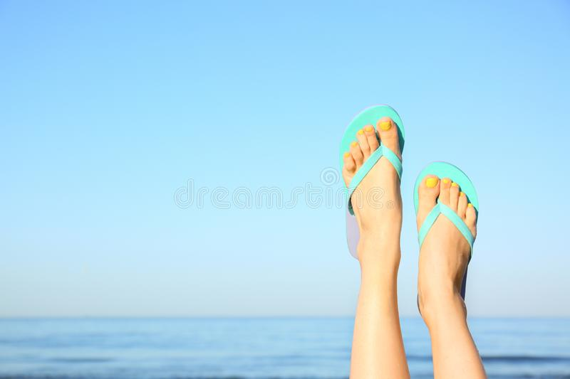 Closeup of woman wearing flip flops near sea, space  text. Beach accessories. Closeup of woman wearing flip flops near sea, space for text. Beach accessories royalty free stock image