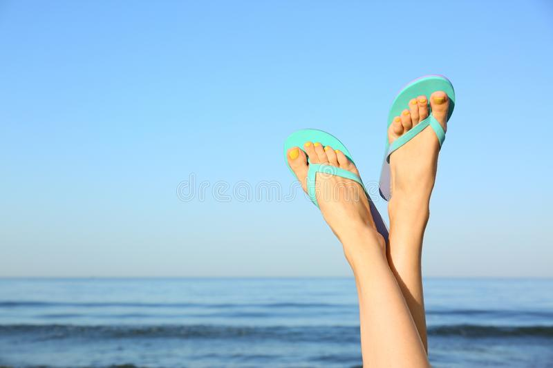 Closeup of woman wearing flip flops near sea, space for text. Beach. Accessories royalty free stock photography