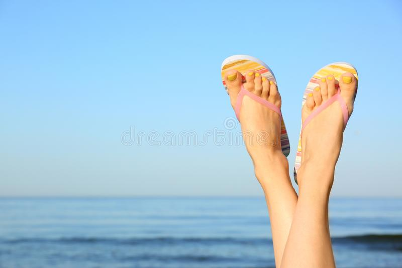 Closeup of woman wearing flip flops near sea, space for text. Beach accessories stock photos