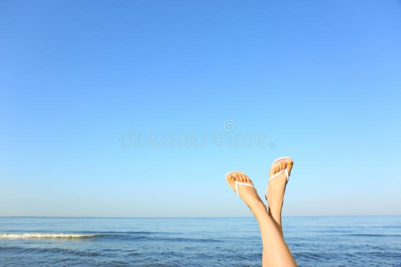 Closeup of woman wearing flip flops near sea, space for text. Beach accessories stock images