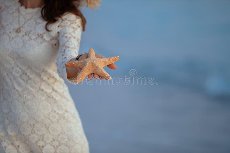 Closeup on woman on seashore at sunset showing starfish royalty free stock image