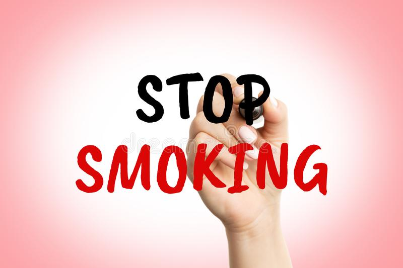 Woman writing stop smoking on screen. Closeup of woman writing stop smoking text with red and blue as health concept on transparent screen royalty free stock images