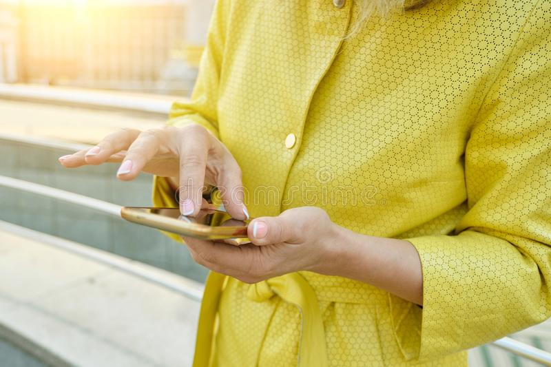 Closeup of womans hand with smartphone, fingers on touchscreen, text message royalty free stock image