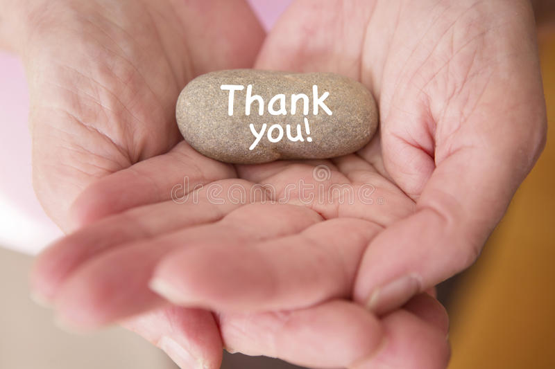 Closeup of womans hands holding stone with words thank you stock photo