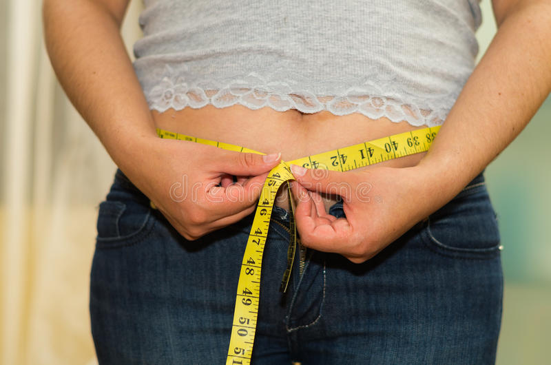 Closeup womans stomach with shirt lifted up, wearing jeans, measuring waistline using measure band, weightloss concept.  stock images