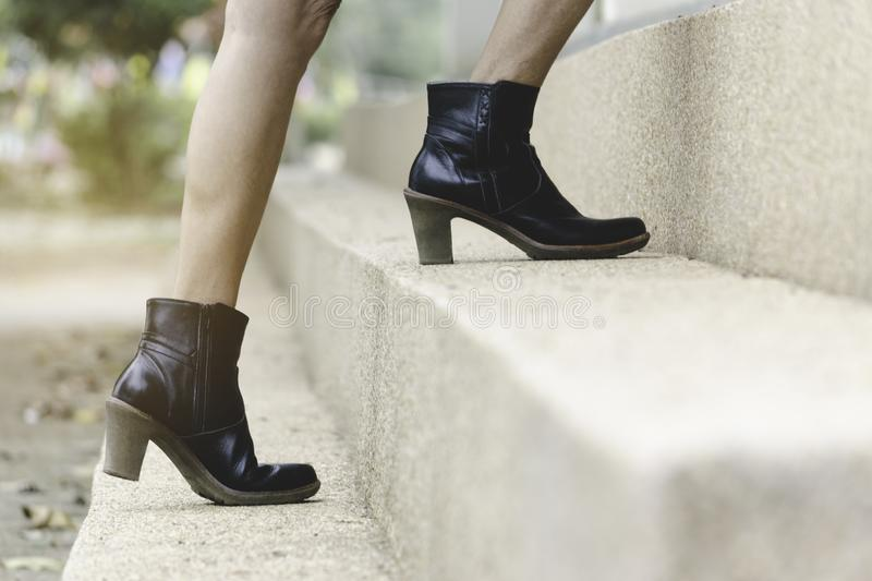 Closeup women legs walking up step in  boots to upstairs.  royalty free stock photo