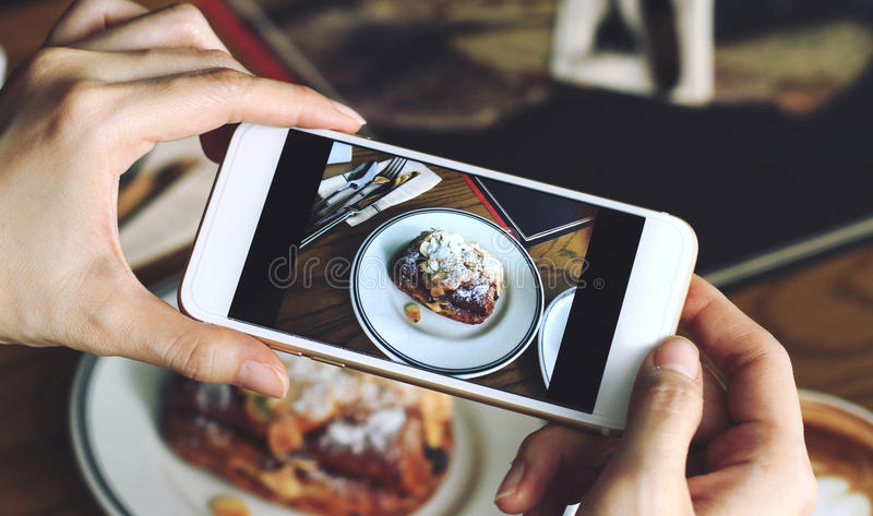 Closeup of women`s hands taking photo of sweet dessert by smartphone. At coffee cafe royalty free stock photography