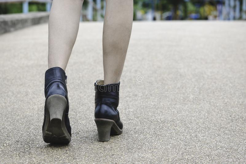 Closeup women walking with boots on road in park.  stock photos