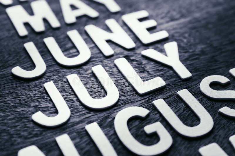 July Wood Letters. Closeup wood letters of July in running name of month stock image