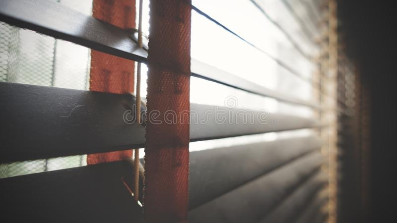 Closeup wooden blind. Sunlight through the windows to the living room.Selective focus and light image backdrop. Evening sun light outside with wooden made from stock photo