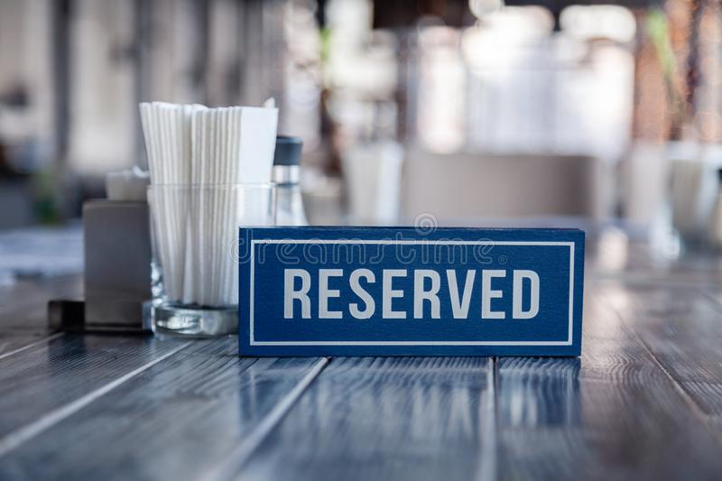 Closeup wooden blue white rectangular plate with the word Reserved standing on gray vintage table in restaurant near to the stock images