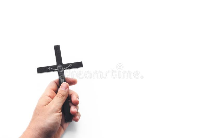 Church utensils. Man holding a crucifix. Closeup of wooden christian cross in the hand on the white isolated background. stock photo