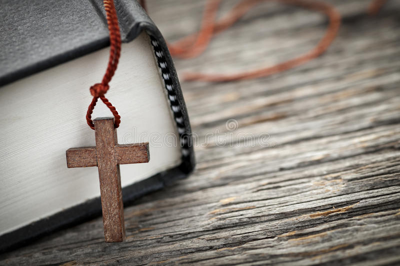 Cross and Bible. Closeup of wooden Christian cross necklace next to holy Bible