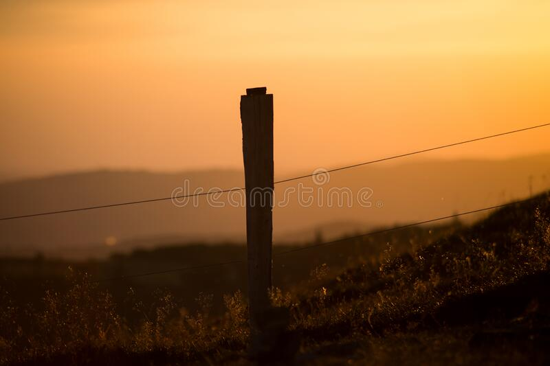 wooden fence silhouette at the top of themountain on sunset background royalty free stock image