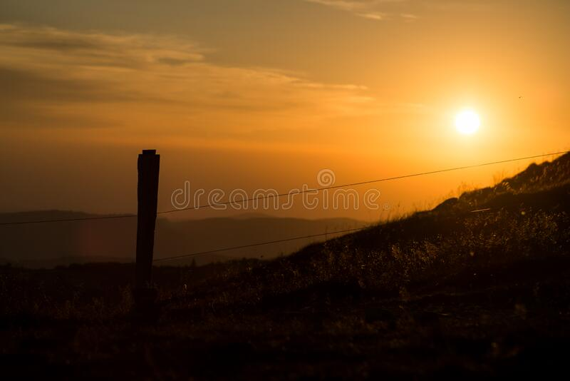wooden fence silhouette at the top of themountain on sunset background royalty free stock images