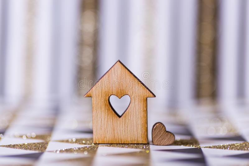 Closeup wooden house with hole in form of heart on geometric abstract background with golden glitter royalty free stock photo