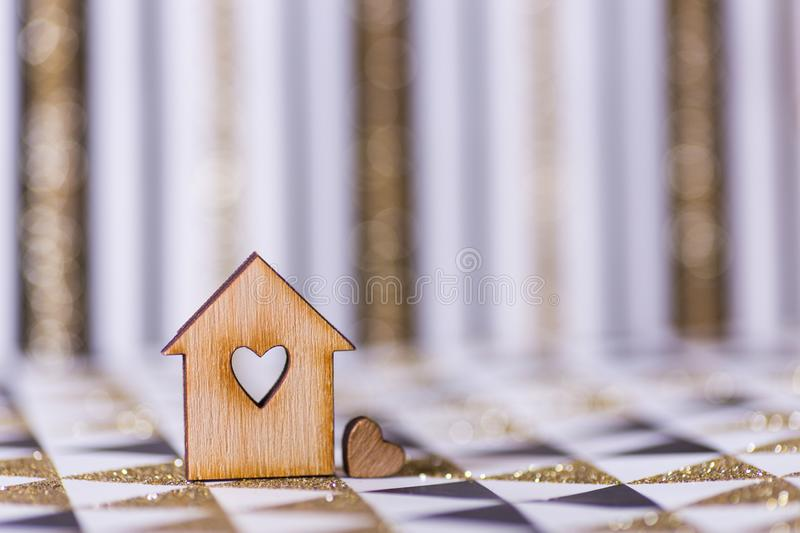 Closeup wooden house with hole in form of heart on geometric abstract background with golden glitter royalty free stock photography
