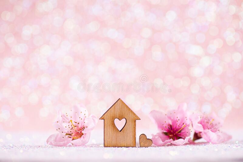 Closeup wooden house with hole in form of heart surrounded by spring flowering tree branches on glitter sparkling pink background. With bokeh. Natural royalty free stock images