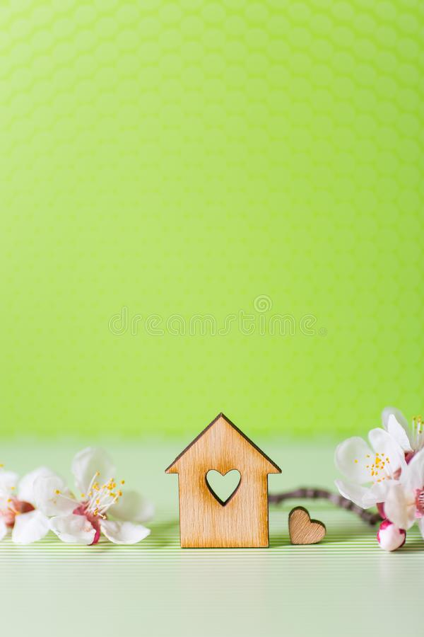 Closeup wooden house with hole in form of heart surrounded by white flowering tree branches on green background. Spring vibrant composition with copy space royalty free stock photography