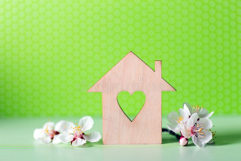 Closeup wooden house with hole in form of heart surrounded by white flowering tree branches on green background. Spring vibrant composition with copy space stock image