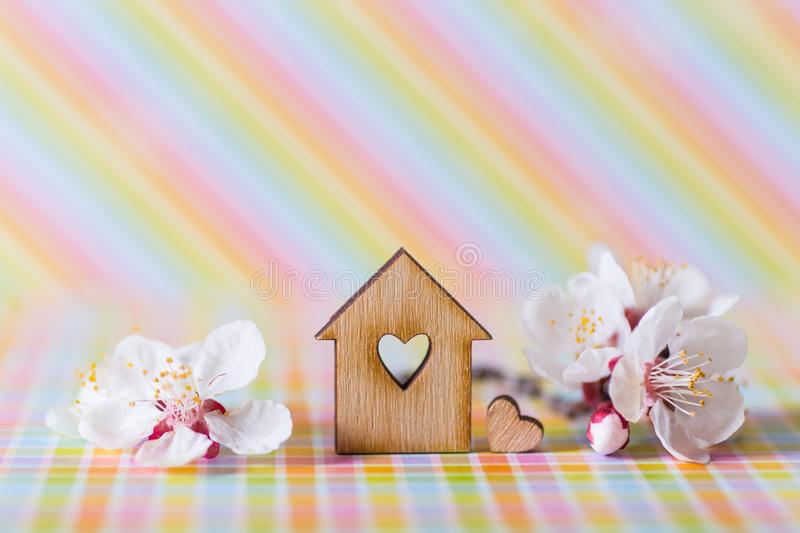 Closeup wooden house with hole in form of heart surrounded by white flowering tree branches on rainbow striped background. Spring vibrant composition with copy stock images