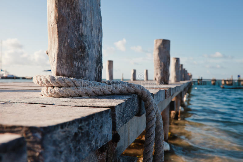 Closeup of wooden pier, blue water,boat rope stock image