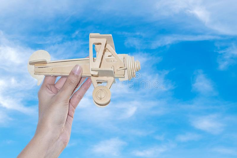 Closeup wooden plane in woman hand with blue sky background stock image