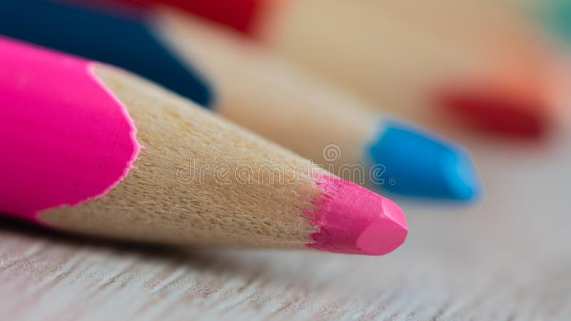 Closeup of wooden sharpened bright pink pencil with the blurry other colored pencils stock image